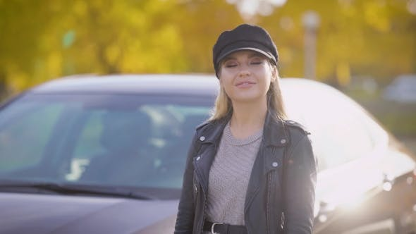 Thumbnail for Stylish Young Woman with Long Straight Blonde Hair Is Wearing Leather Cap Is Standing on a Fall