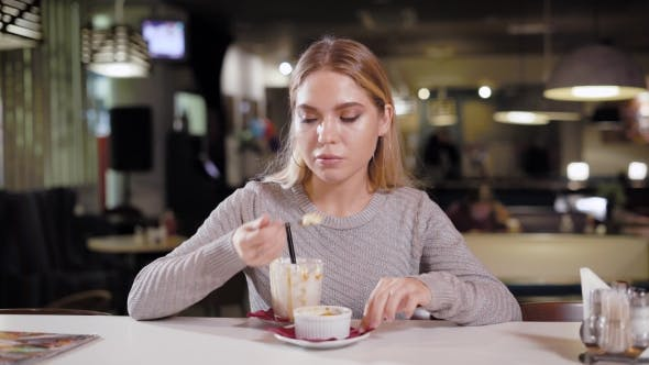 Thumbnail for Lonely Pretty Girl with Blonde Hair Is Having a Coffee Break During a Day, Eating Cake