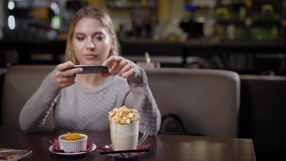 Thumbnail for Joyful Young Woman with Blonde Hair Is Taking Photo of Her Cake and Coffee By Phone
