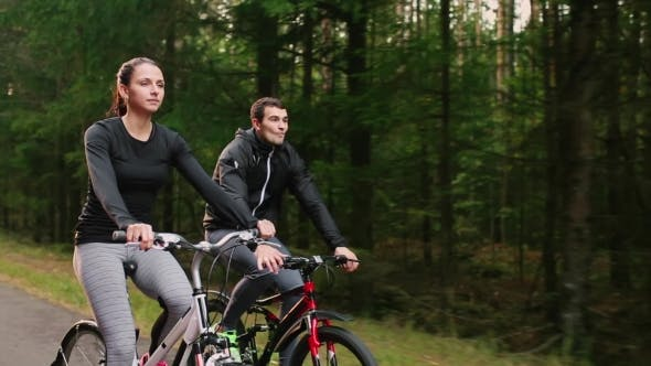 Thumbnail for Young Couple Enjoying Cycling Through Park in Summer