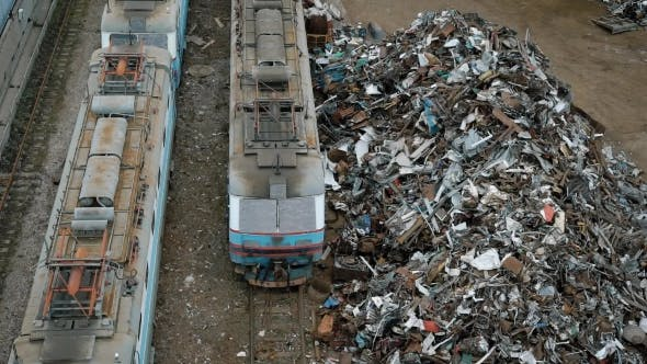 Thumbnail for Large Heaps of Metal Scrap and Containers with Garbage Are Near a Railway with Trains