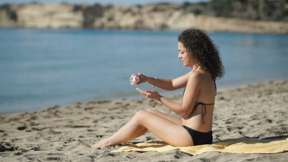 Thumbnail for A Young Girl Smears Sunscreen on the Beach