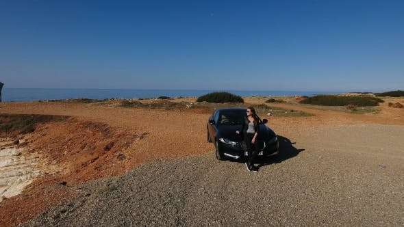 Thumbnail for Pretty Woman in Black Sits on Car Hood and Enjoys the View on Blue Sea