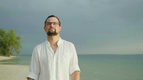A Young Man in an Easy Shirt Walks Along the Beach