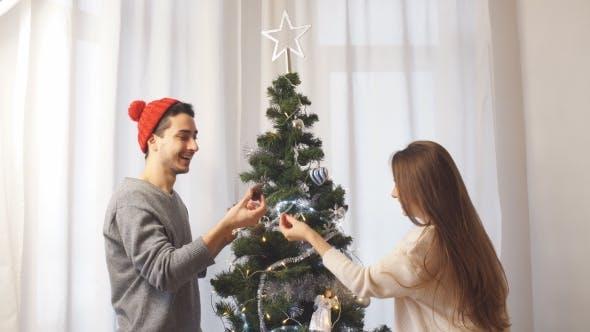 Thumbnail for Glückliches junges Paar Dekoration Weihnachtsbaum in niedlichen Pullover