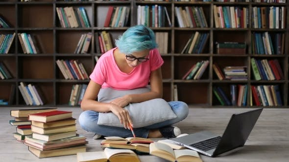 Cover Image for Female Student Researching with Books and Laptop