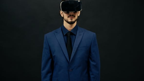 Cover Image for Man in Suit Wearing VR Headset on Black Studio Background Experiencing Virtual Reality