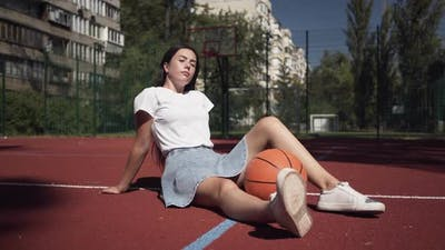 Cute Teen Brunette Girl with a Basketball Ball Looking at the Camera Sitting on the Basketball Court