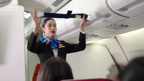 Asian female flight attendant showing safety demonstration on airplane