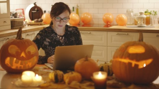 Thumbnail for Woman Using Laptop Near Halloween Decorations
