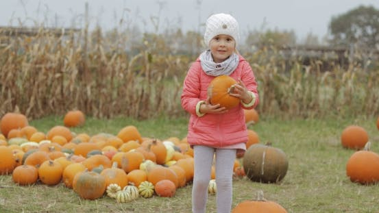 Thumbnail for Girl Posing with Bright Pumpkin in Yard
