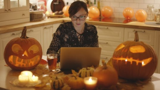 Thumbnail for Frau mit Laptop inmitten Halloween-Dekorationen