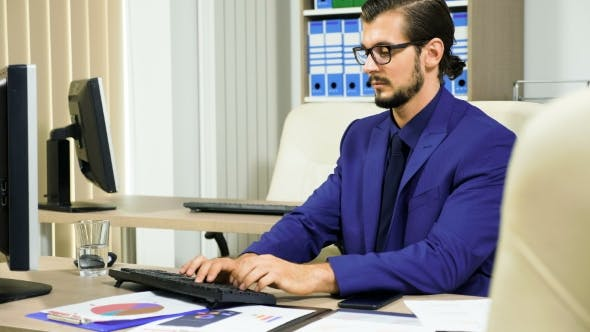 Thumbnail for Businessman Working on the Computer and Talking on the Phone