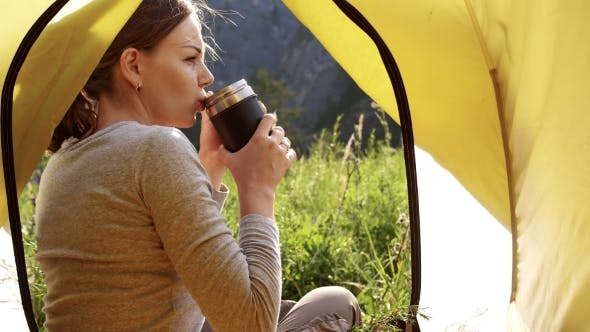 Thumbnail for Girl Is Drinking Tea From a Mug of Thermos on the Background of Mountains