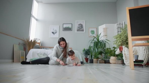 Thumbnail for Mother with a Child in the White Interior of His Home To Collect the Jigsaw Puzzle Together with His
