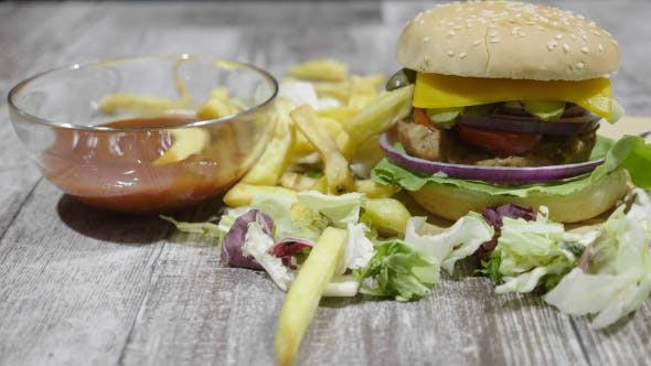 Thumbnail for Delicious French Fries Falling Over a Burger Next To Cola and Ketchup