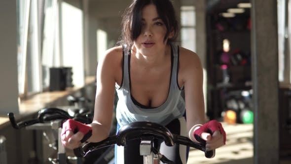 Attractive Woman Enhancing Her Endurance While Working Out on an Exercycle