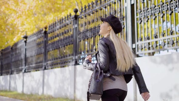 Thumbnail for Trendy Woman Enjoying Stroll in Autumnal Park Walking Down Street