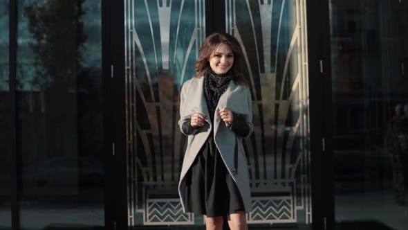 Thumbnail for Charming Young Woman Walks Through the Autumn City in a Coat and Smiles. Cute Girl on a Background