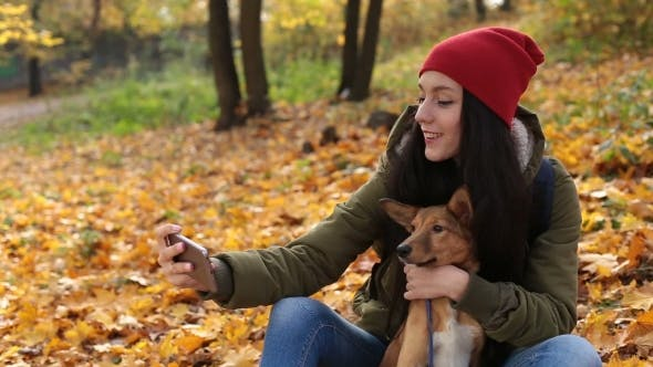 Cover Image for Smiling Woman with Dog Taking Selfie in Autumn