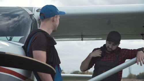 Pilot and Mechanic Chatting on an Airfield