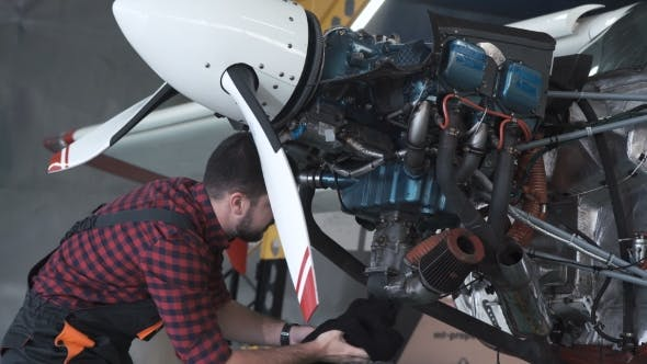 Thumbnail for Man Cleaning Aircraft Engine in Hangar