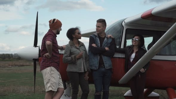 Thumbnail for Group of Friends Talking Next To Airplane