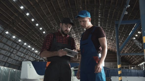 Thumbnail for Two Men Discussing in Aircraft Hangar