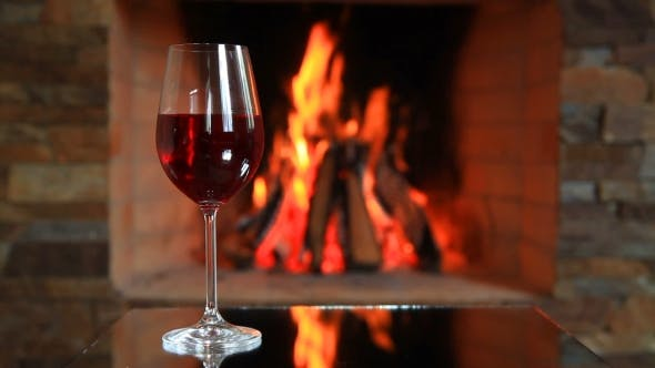 Cover Image for Wineglass with Red Wine Near a Fireplace