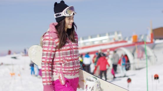 Thumbnail for Young Woman Walking with Snowboard