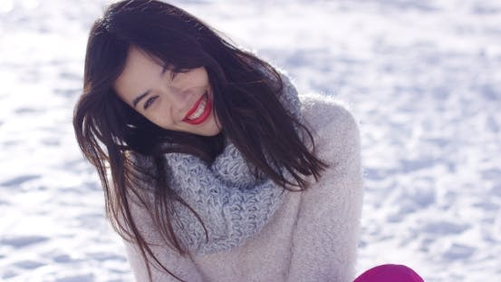 Thumbnail for Happy Woman Sitting on Snow