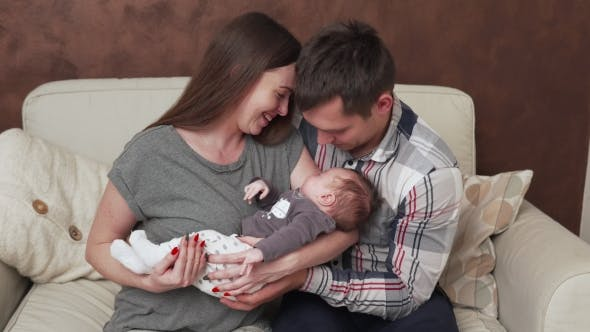 Thumbnail for Happy Family with Newborn Baby on Sofa at Home