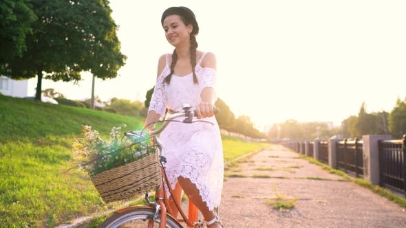 Thumbnail for Young Beautiful Woman Riding a Bicycle at Sunset