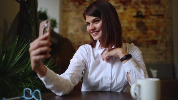 Thumbnail for Ein schönes Mädchen sitzt in einem Café und nach betrunken ein heißer Kaffee, Posen für eine Handy-Kamera zu machen