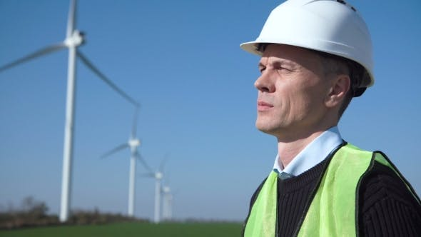Thumbnail for Thoughful Engineer Against Wind Turbine