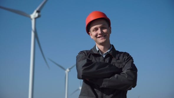 Thumbnail for Smiling Engineer Standing Against Wind Farm