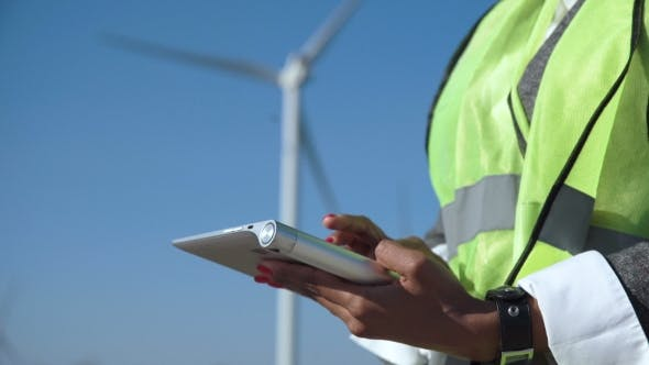 Thumbnail for Engineer Using Digital Tablet Against Wind Turbine