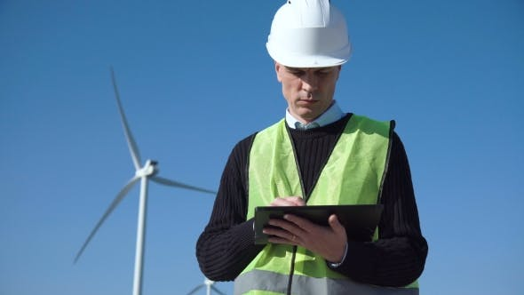 Thumbnail for Engineer Using Digital Tablet Against Wind Turbine