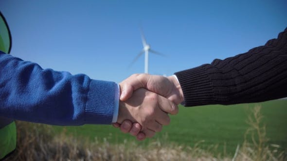 Cover Image for Business Handshake Against Wind Turbines