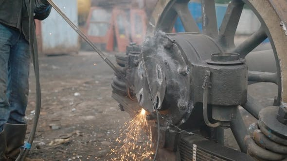 Thumbnail for Industrial Worker Using Cutting Torch To Separate Metal Parts of Truck's Wheels