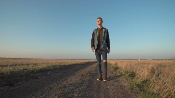 Thumbnail for Young Man Walking Away Down a Rural Road