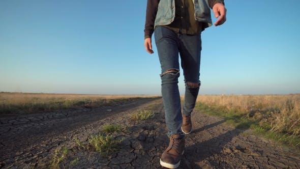 Unknown Man Walking Away Down a Rural Road