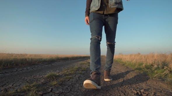 Homme inconnu marchant loin vers le bas une route rurale