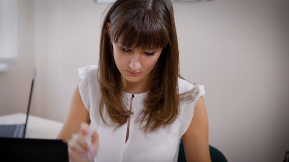 Thumbnail for Young Brown-haired Woman Accountant Is Checking Invoices and Statements in an Office During Working