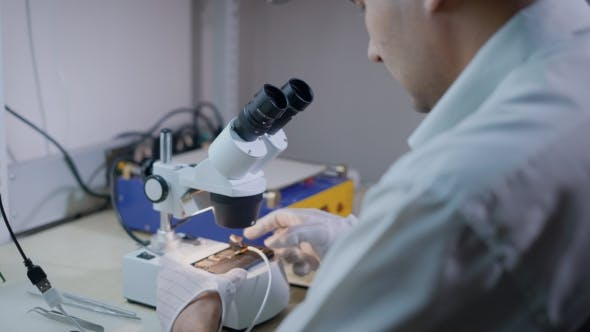 Thumbnail for Electronic Engineer Is Examining Mobile Phone Under a Microscope, Repairing Mechanism