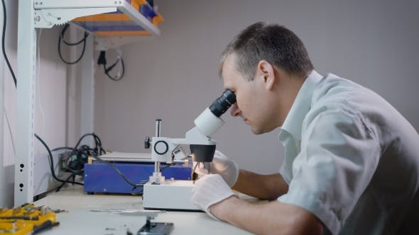 Thumbnail for Electronic Engineer Is Looking on a Microscope in Laboratory and Studying Small Mechanism