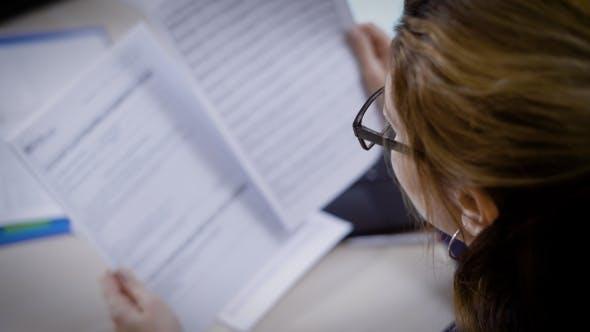 Thumbnail for Eine Anwältin Frau trägt eine Brille liest tagsüber Dokumente in ihrem Büro