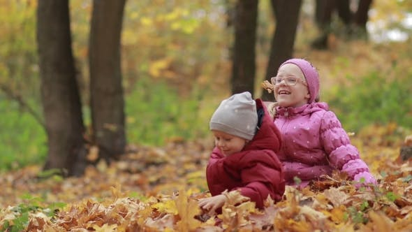 Cheerful Children Playing in Leaves Pile in Autumn