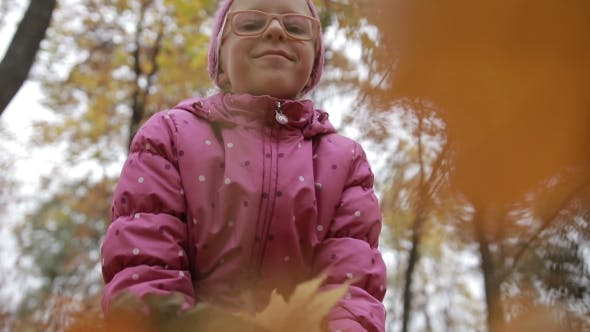 Thumbnail for Smiling Girl Throwing Maple Leaves in Autumn