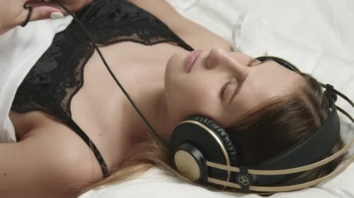 Sensual Woman in Bed with Large Headphones on